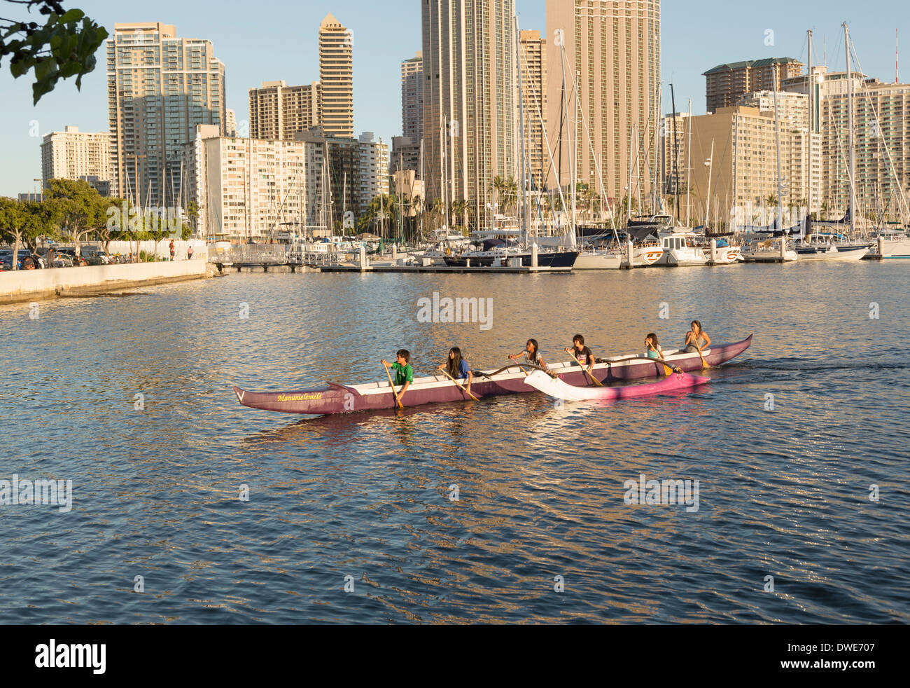 Honolulu, Hawaii, USA - Group of boys and girls paddle an outrigger Hawaiian canoe in the harbor by Ala Moana beach park - Stock Image