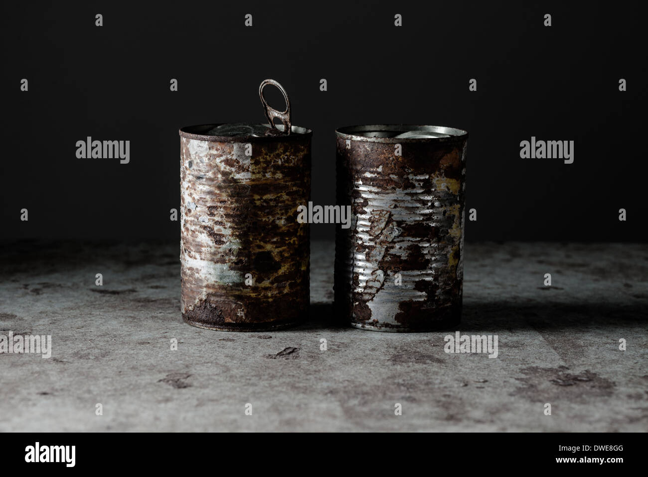 Two Rusted Cans on Dirty Surface - Stock Image