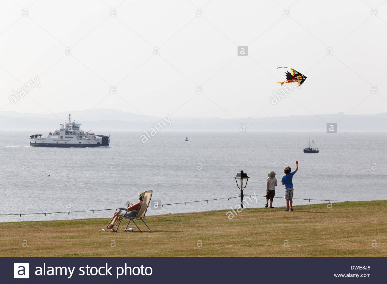Two boys flying a kite and a woman sunbathing in the seaside town of Largs beside the Firth of Clyde, Scotland, UK - Stock Image
