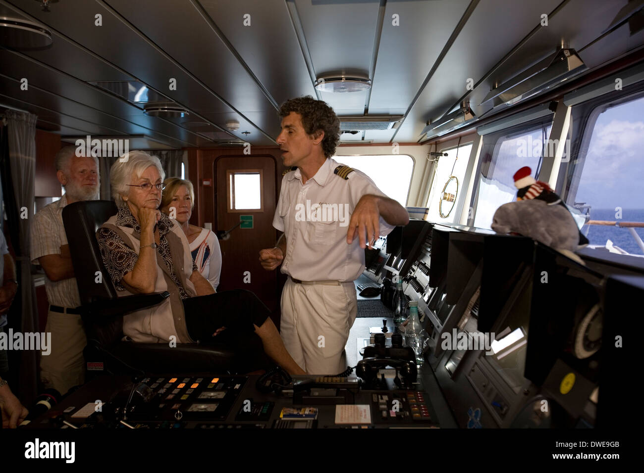 Captain Steffen Freidrich discusses the operation of the expedition cruiser Orion with passengers during a customary bridge tour - Stock Image