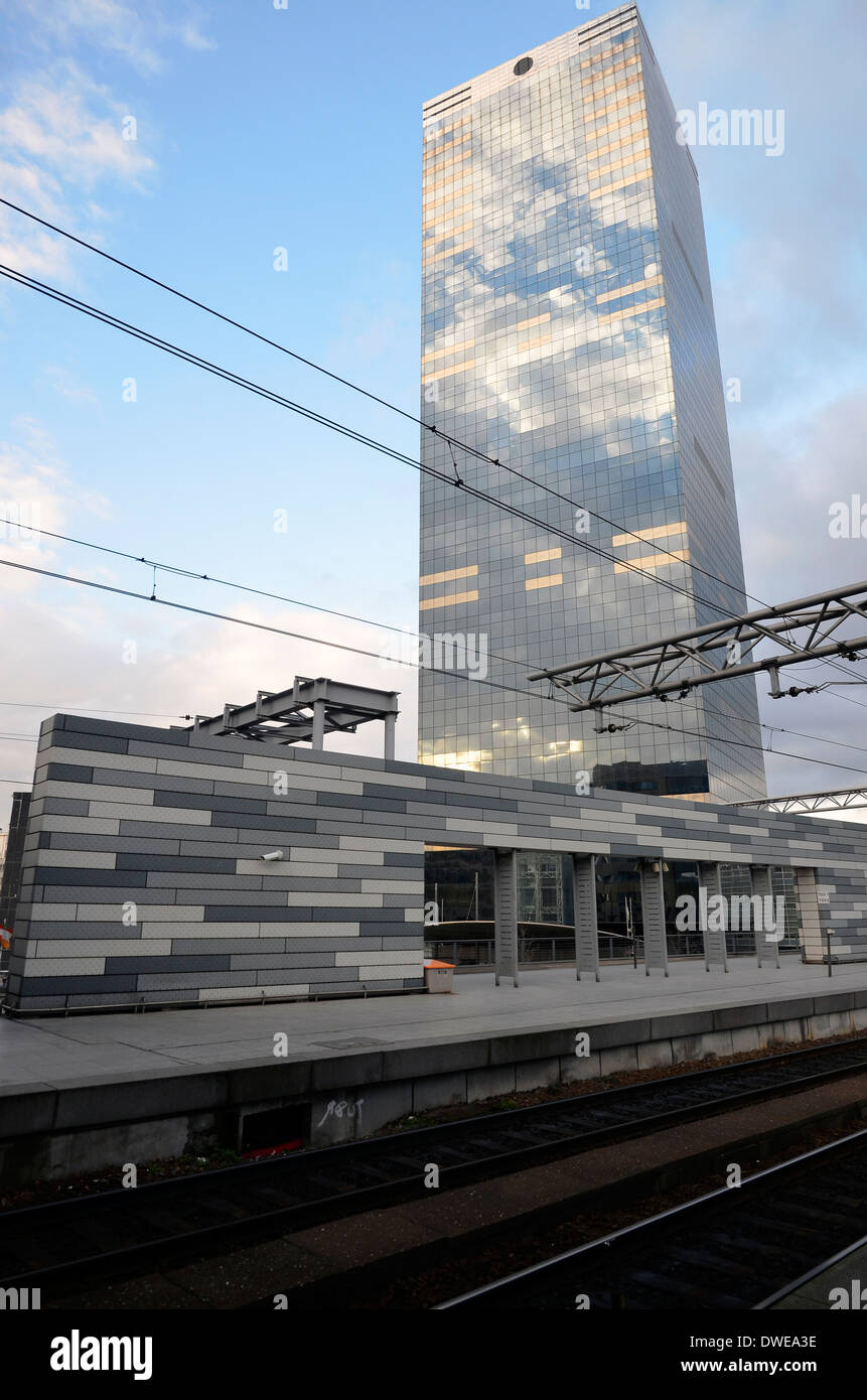 Overhead catenary at Brussels Midi railway station with steel and glass office block behind. Stock Photo