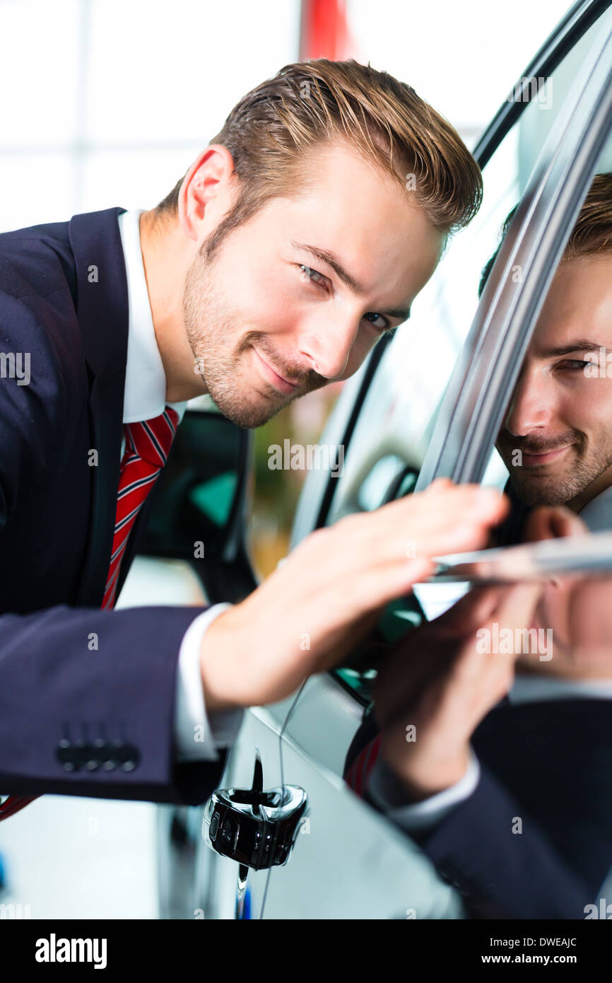 Seller or car salesman in car dealership presenting the reflecting car paint of his new and used cars in the showroom - Stock Image