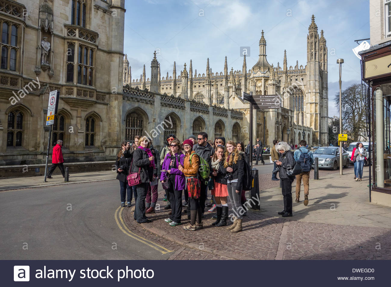 A group of tourists pause with their tour guide on Kings Parade with Kings College in the background. - Stock Image