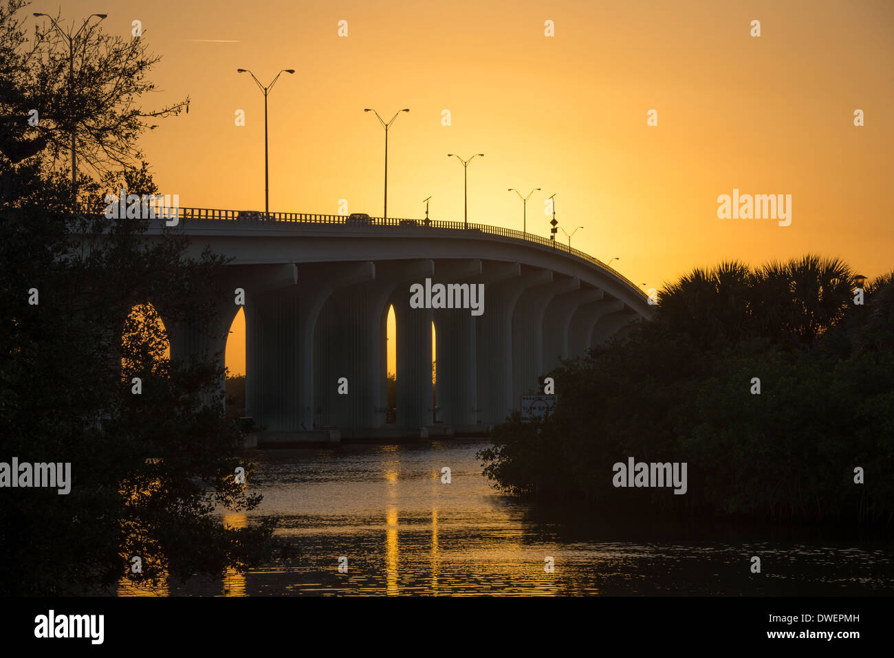 As the sun sets, traffic heads across the bridge and  over the Indian River in Vero Beach, Florida. - Stock Image