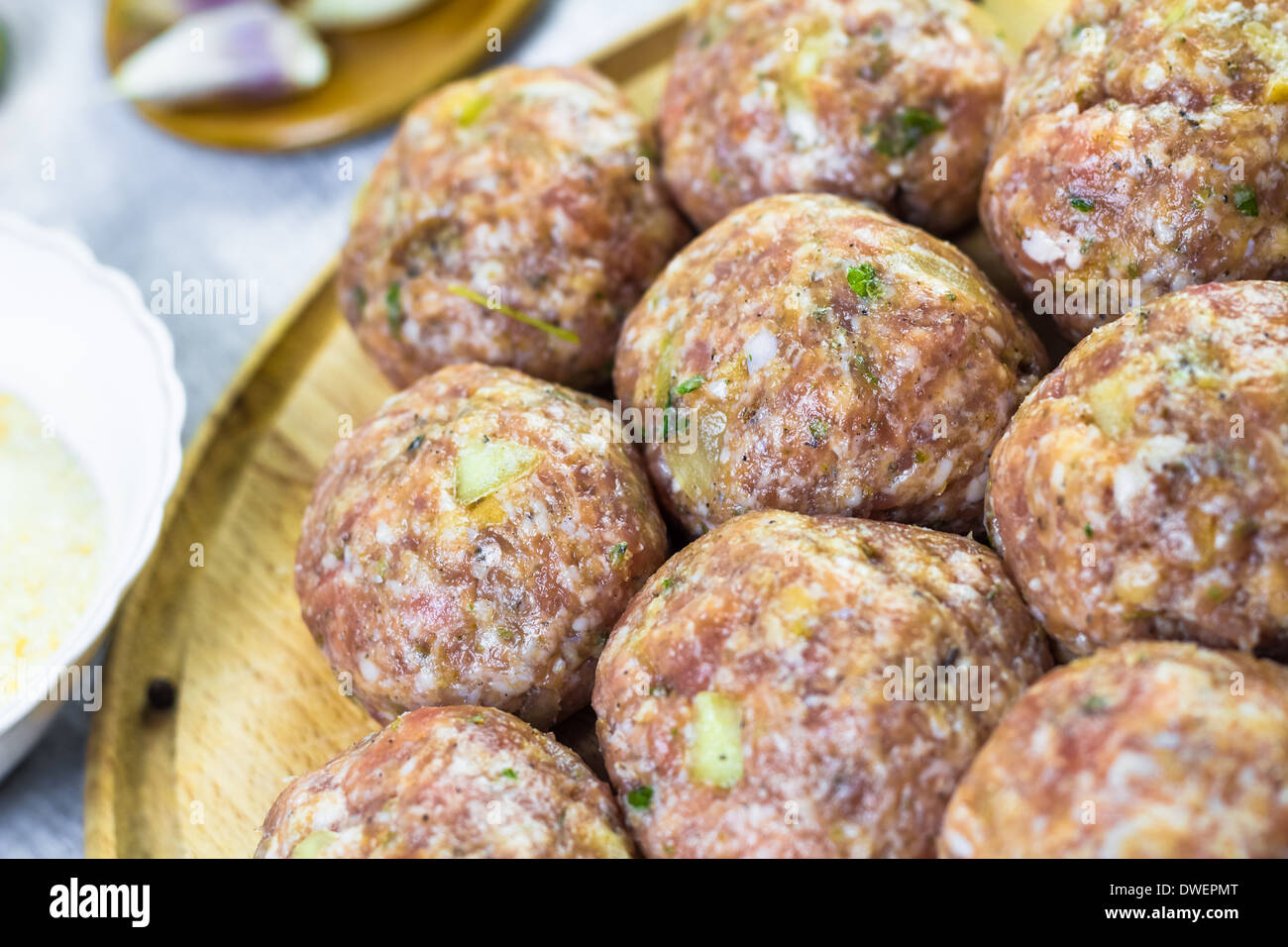 Raw meat balls of minced beef prepared for roll in breadcrumbs - Stock Image
