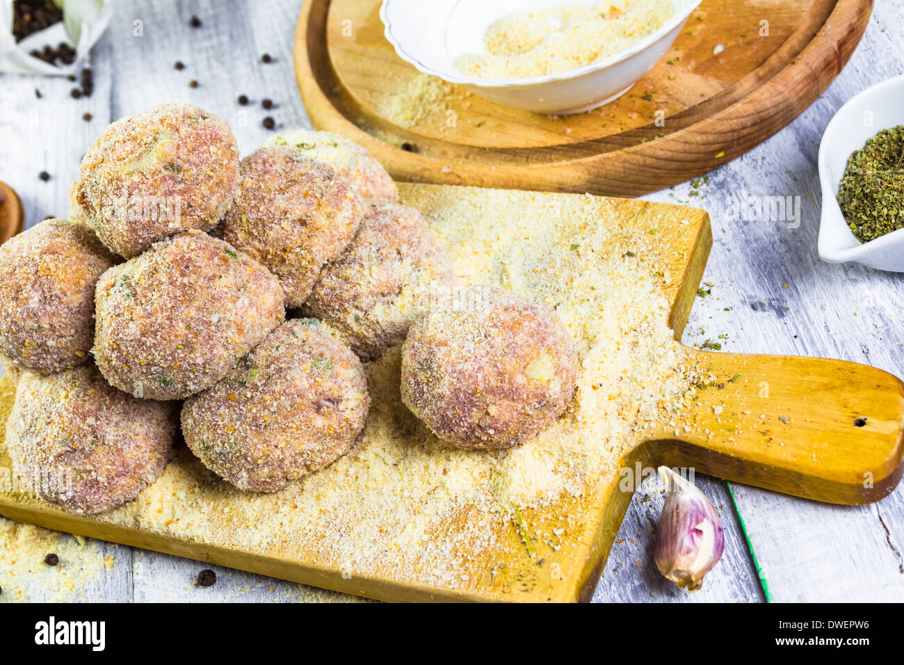 Raw meat balls of minced beef with rolled in breadcrumbs - Stock Image