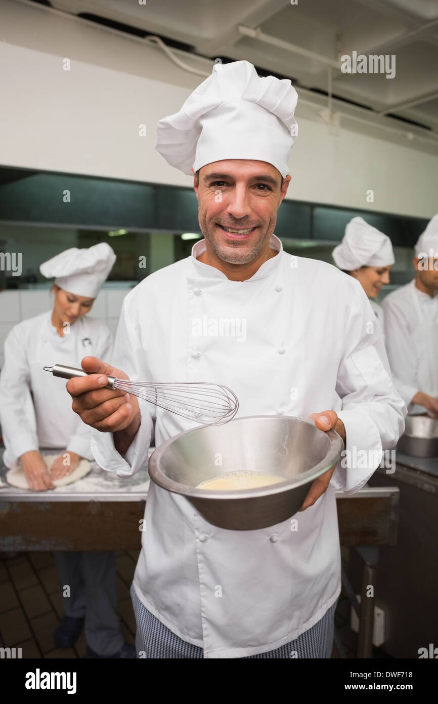 Happy chef whisking bowl of eggs smiling at camera - Stock Image