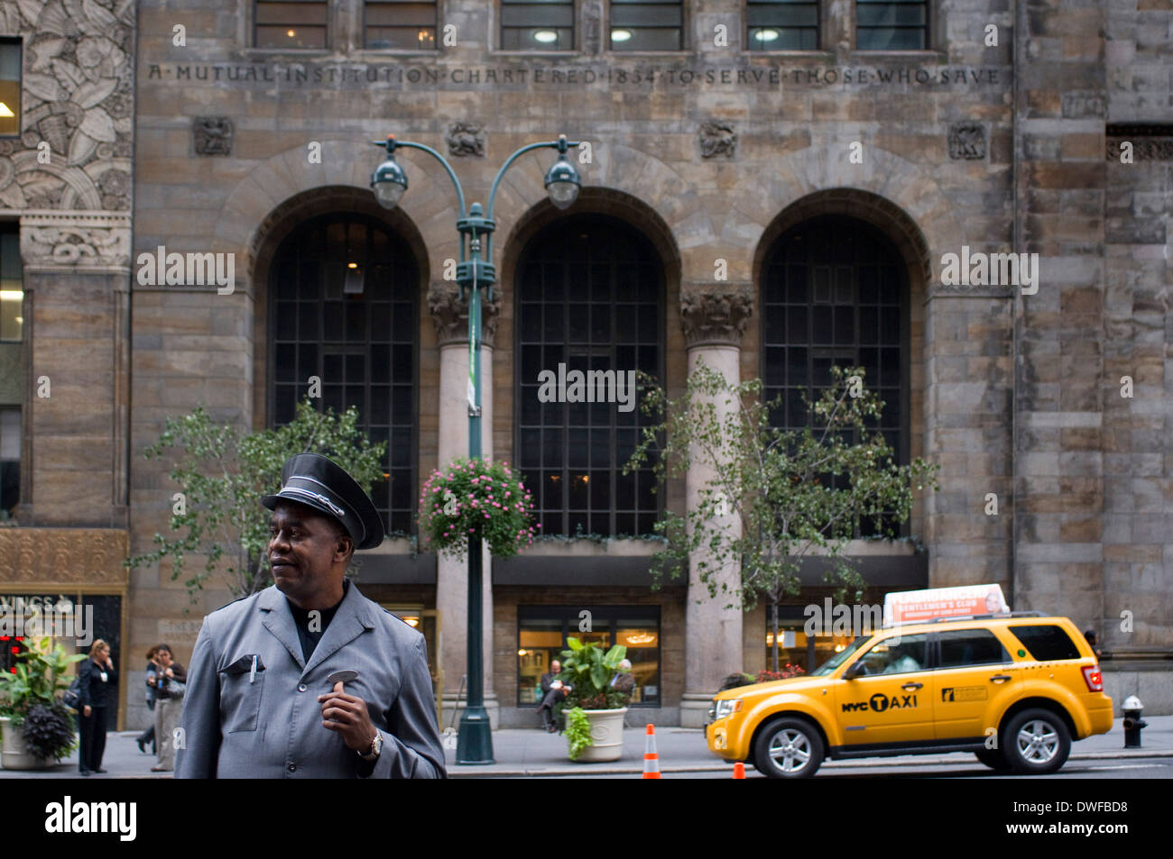 A bellboy at a nearby hotel facing the front of Home Saving of America in Lower Midtown. 110 E 42nd Street. This building built - Stock Image
