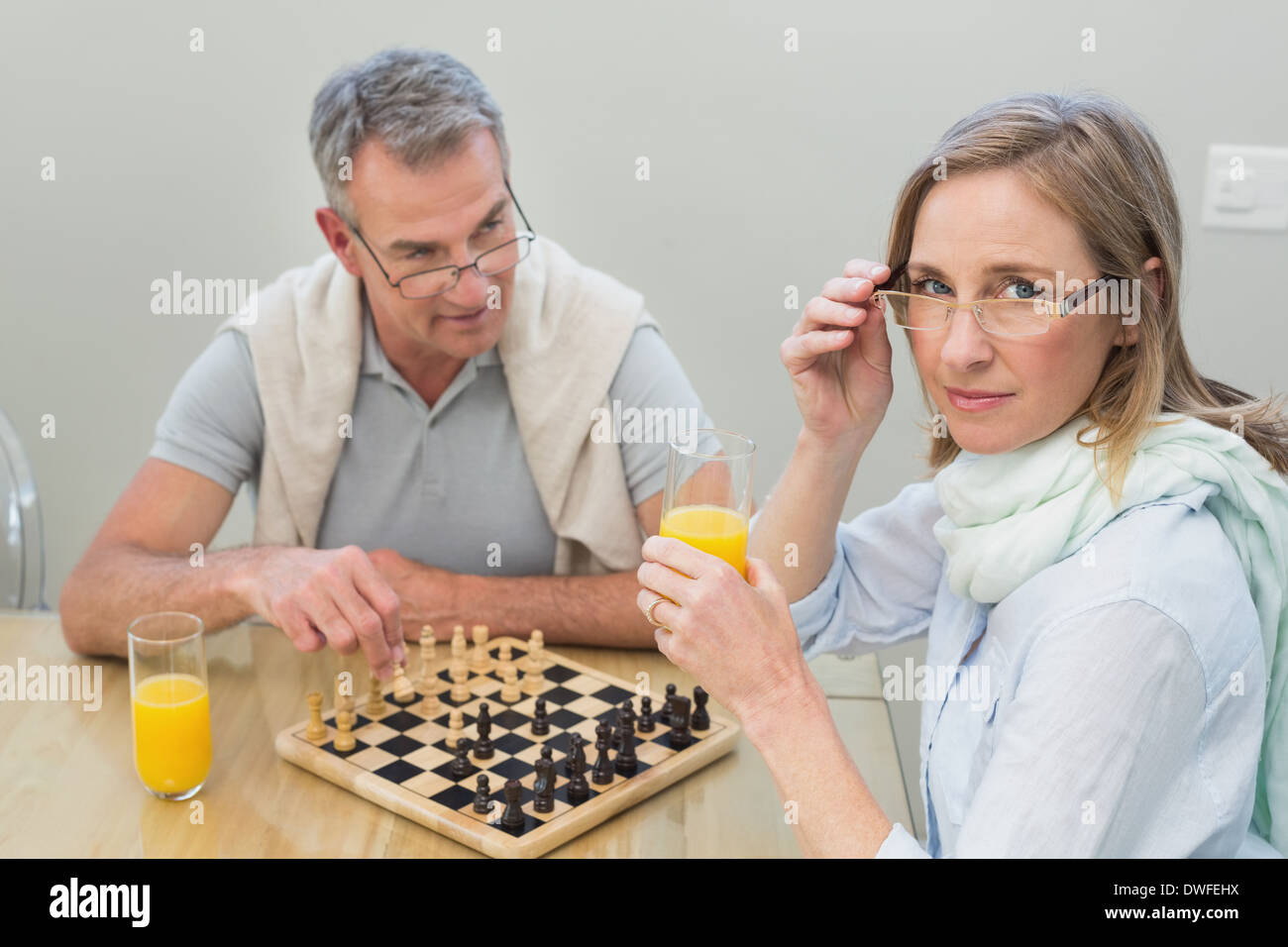 Couple playing chess while having orange juice - Stock Image