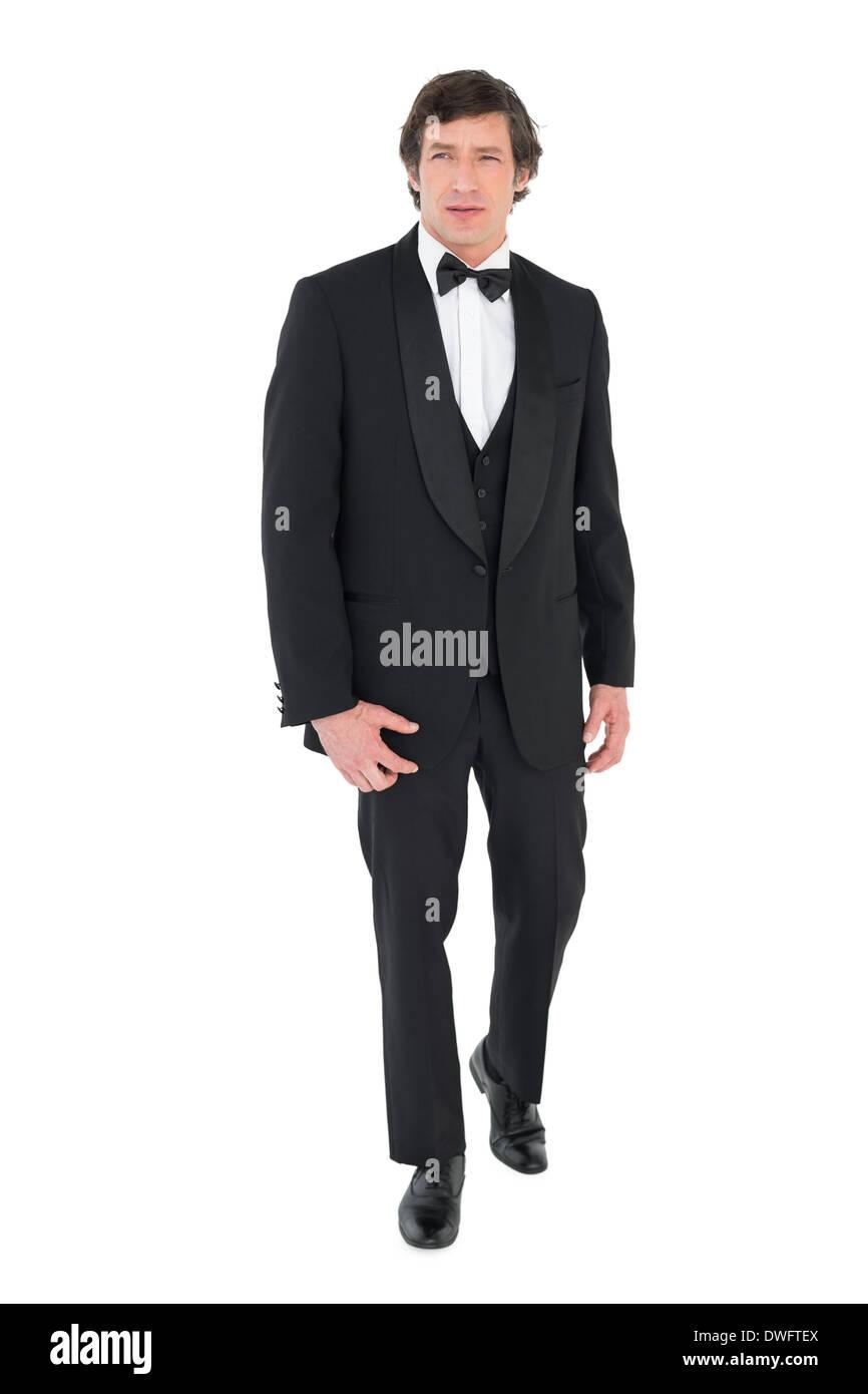 Groom in tuxedo walking over white background - Stock Image