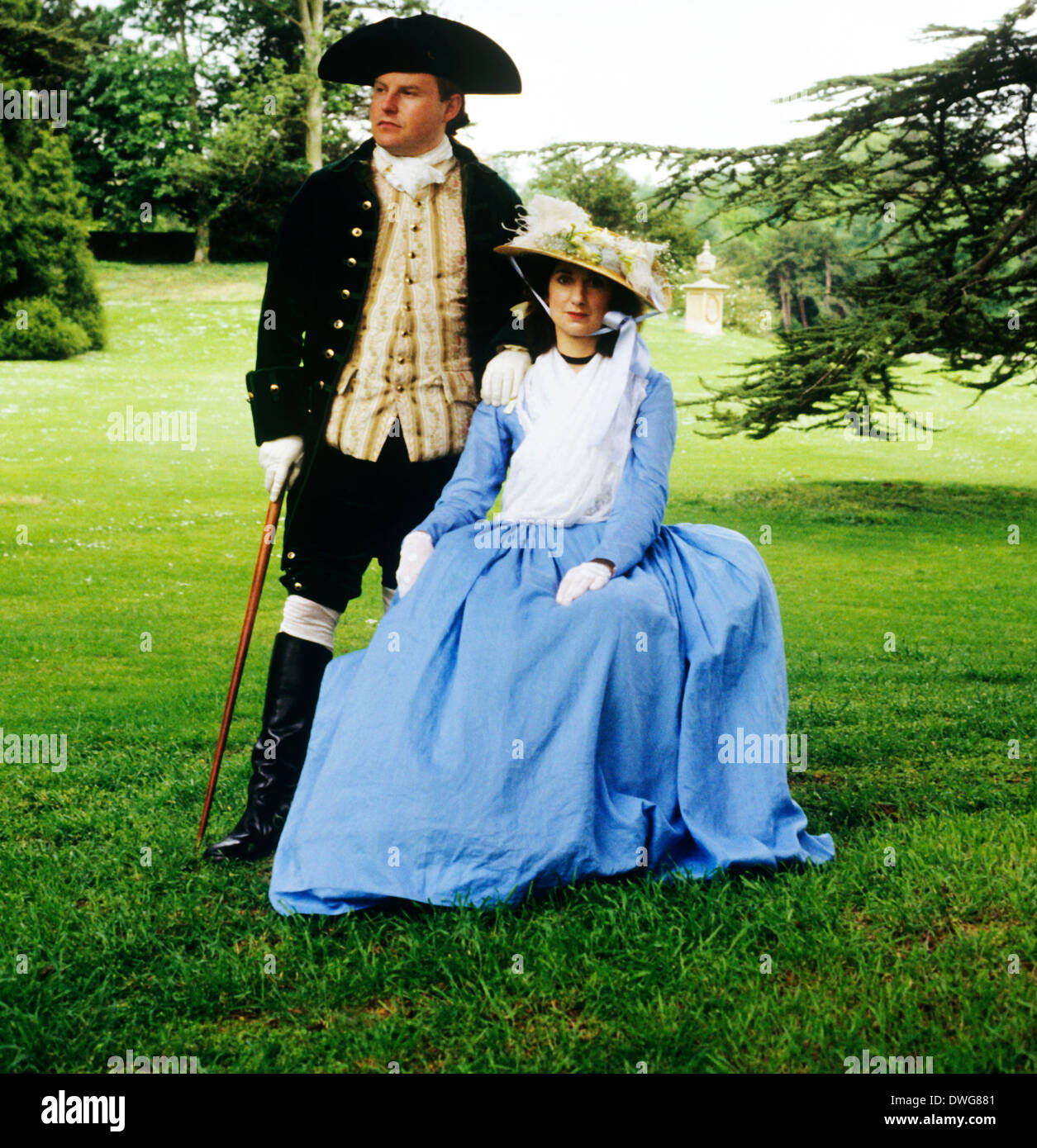 18th Century English Gentry in landscaped parkland, Audley End House gardens, Essex England UK, historical re-enactment costume costumes fashion fashions gentleman and lady - Stock Image