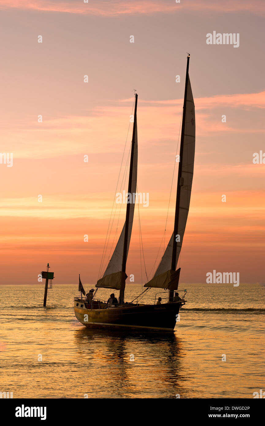 ketch with sails up returning to Venice Florida harbor at sunset on a flat sea - Stock Image