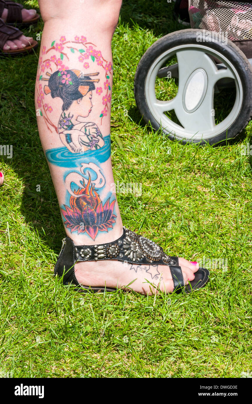 Young British womans right leg with large tattoo of Asian girl. it is estimated that over 40% of adults in Britain have a tattoo Stock Photo