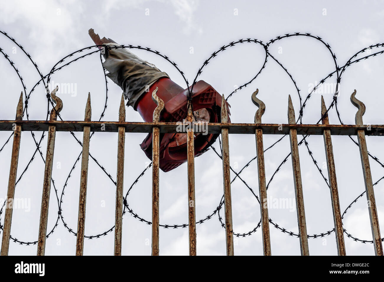 Battered Traffic cone trapped in barbed wire of Security fence in St George's Road, South London - Stock Image