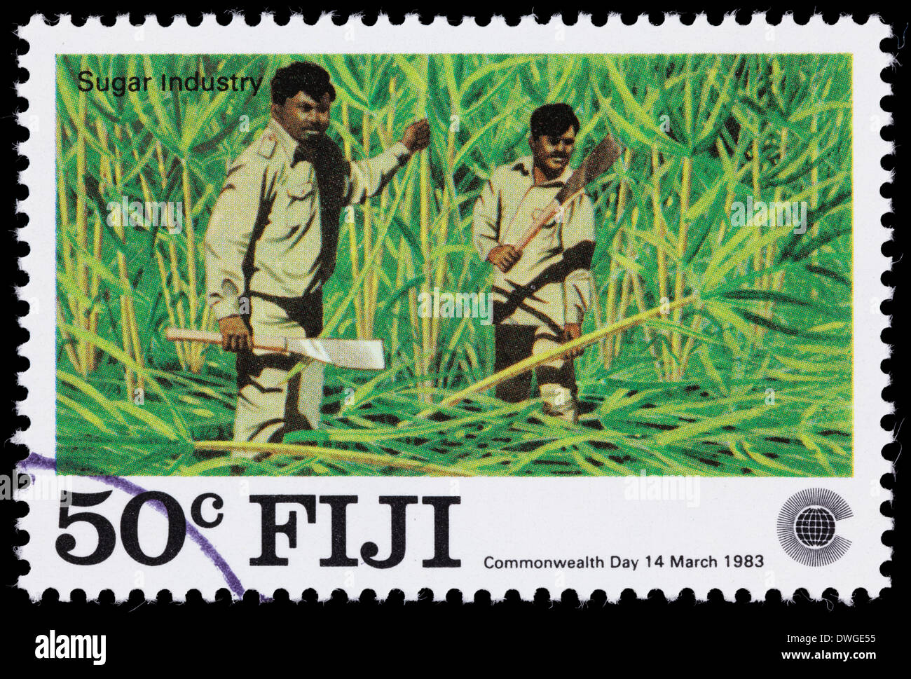 A 1983 Fiji postage stamp with an illustration of two mean harvesting sugar cane. - Stock Image