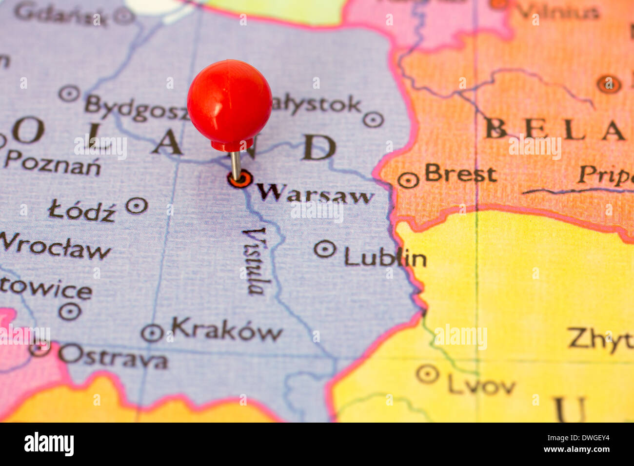 Round red thumb tack pinched through city of Warsaw on Poland map ...