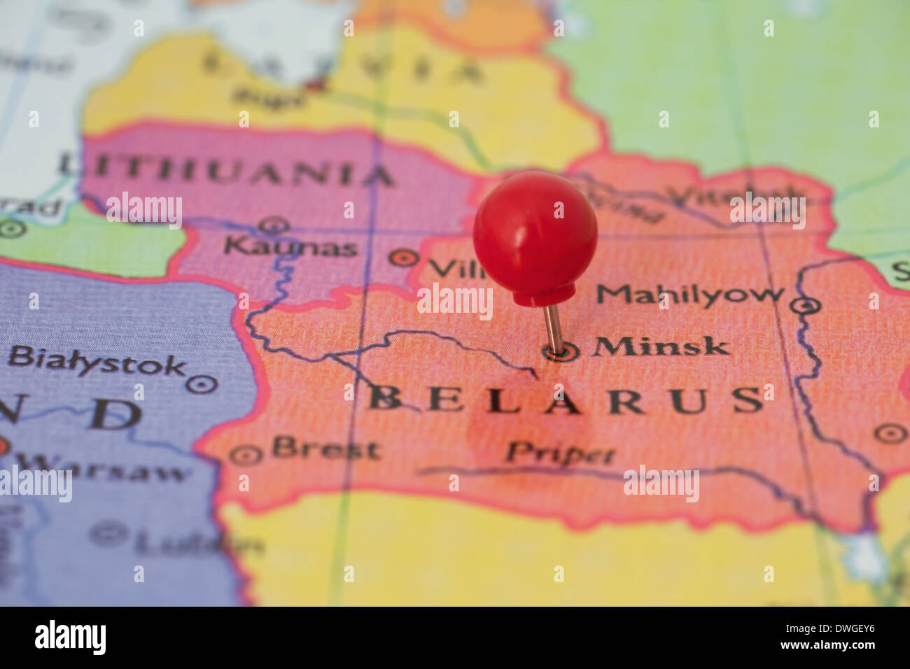 Round red thumb tack pinched through city of Minsk on Belarus map. Part of collection covering all major capitals of Europe. - Stock Image
