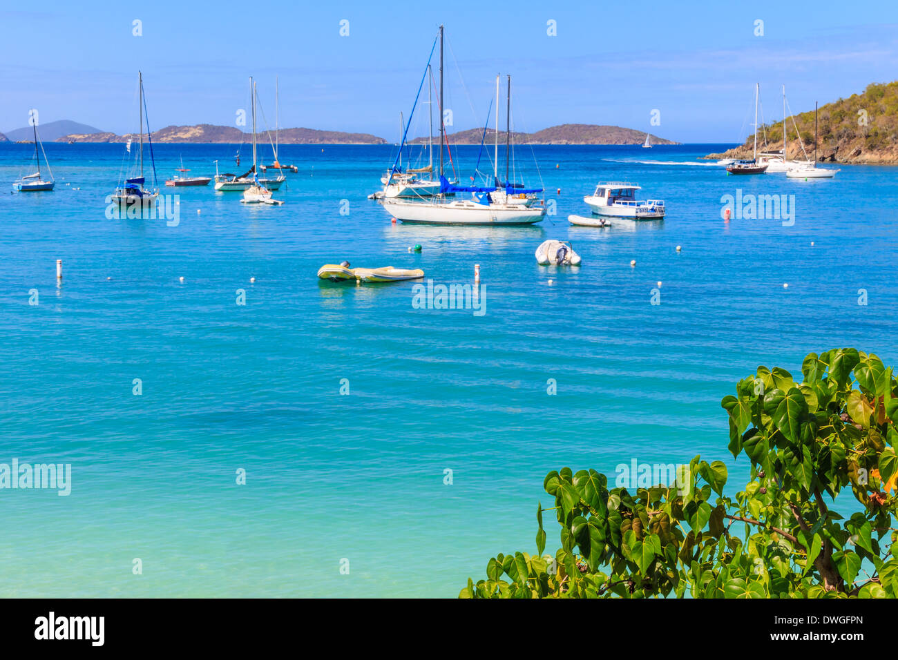 Sailboats and power boats anchored in crystal clear turquoise waters in the Caribbean - Stock Image