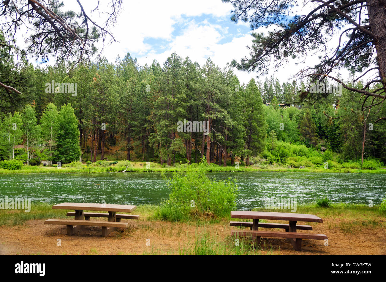 Deschutes River in Central Oregon slowing meandering past a pair of picnic tables - Stock Image