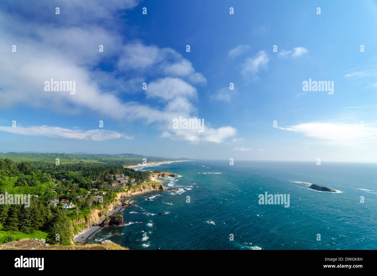 Lush green Oregon coast with blue sky and Pacific Ocean - Stock Image