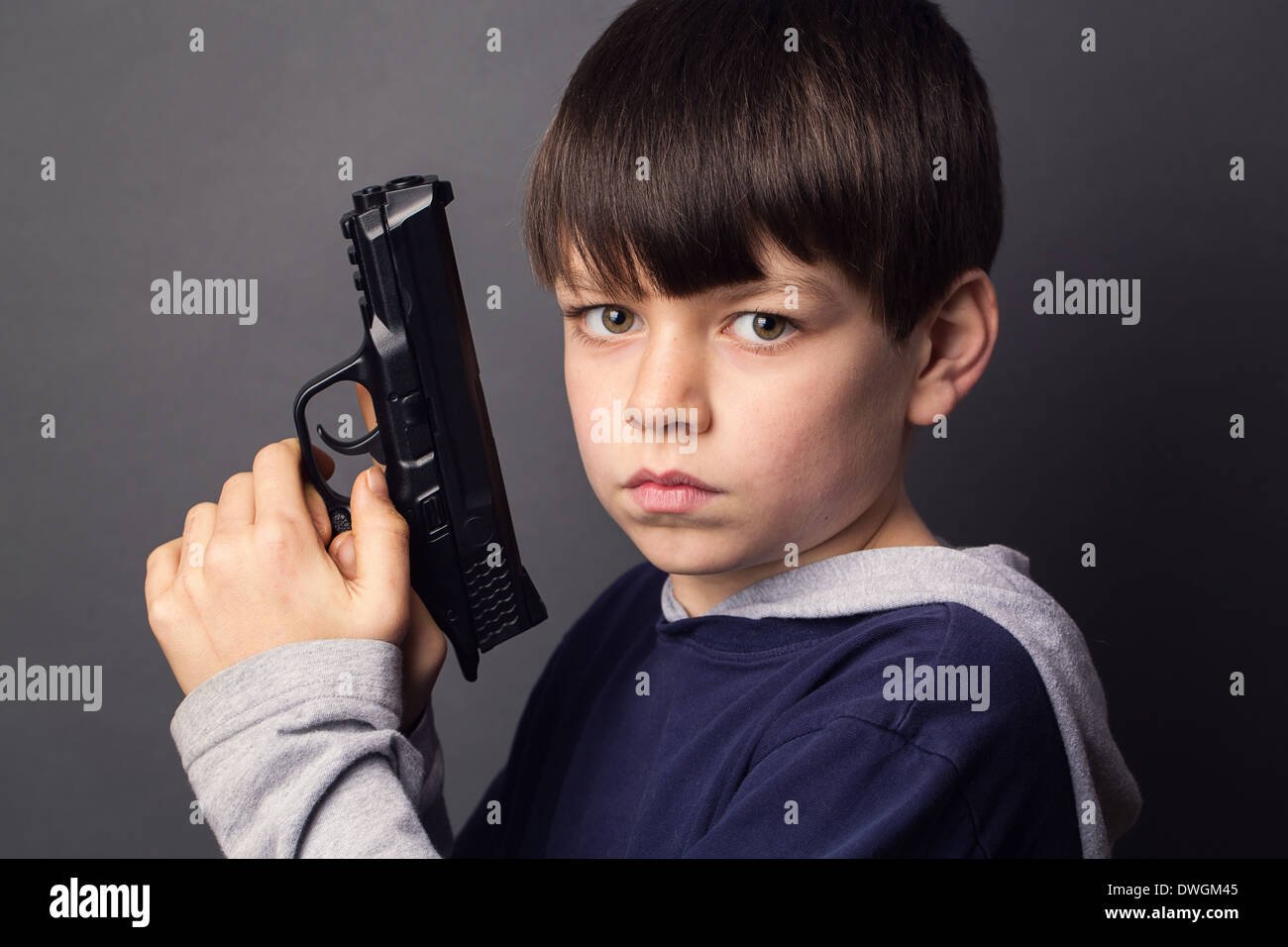 A young boy holds/points a handgun - Stock Image