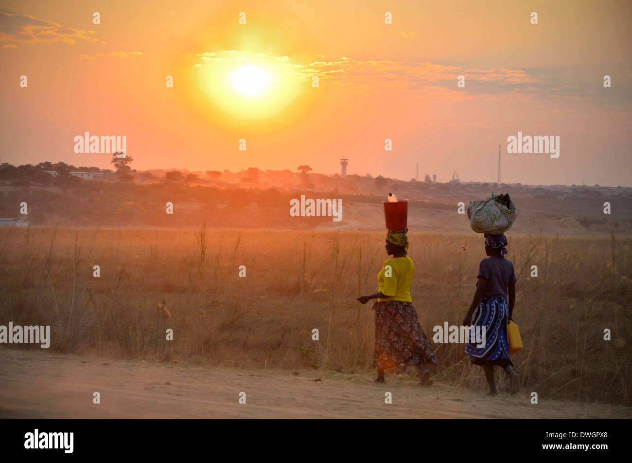 Women carrying water on head at sunset. Cuito Cuanavale, Angola, Africa. - Stock Image