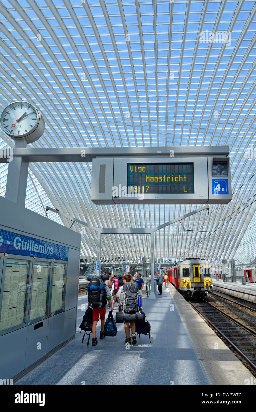 Backpacker group train station platform loaded with backpack kit in modern public transport glass roof building departures board & clock Belgium Liege - Stock Image