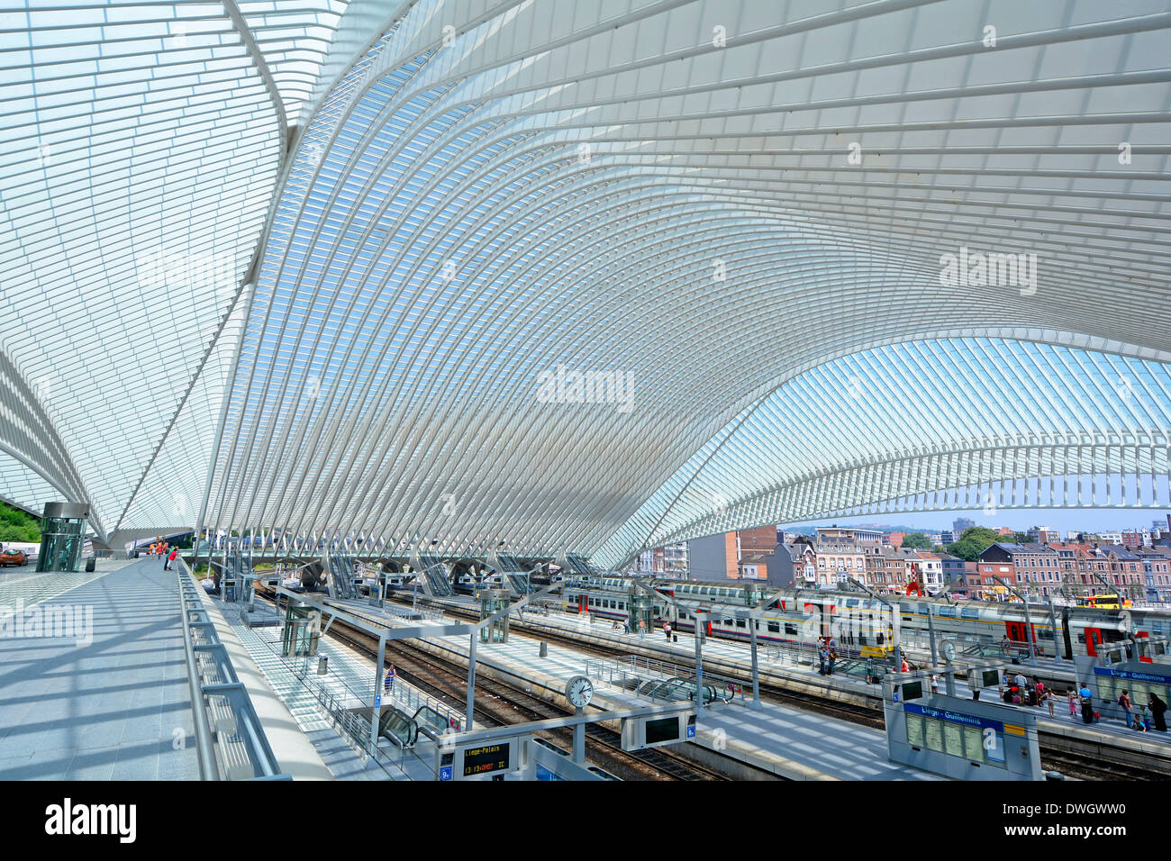 Glass ceiling at modern public transport infrastructure building curved over Belgium train station railway track & platform town of Liège EU beyond - Stock Image