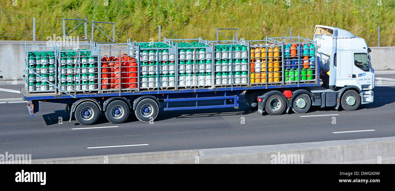 Flo Gas delivery trailer and lorry with mixed load of butane and propane cylinders driving along motorway - Stock Image