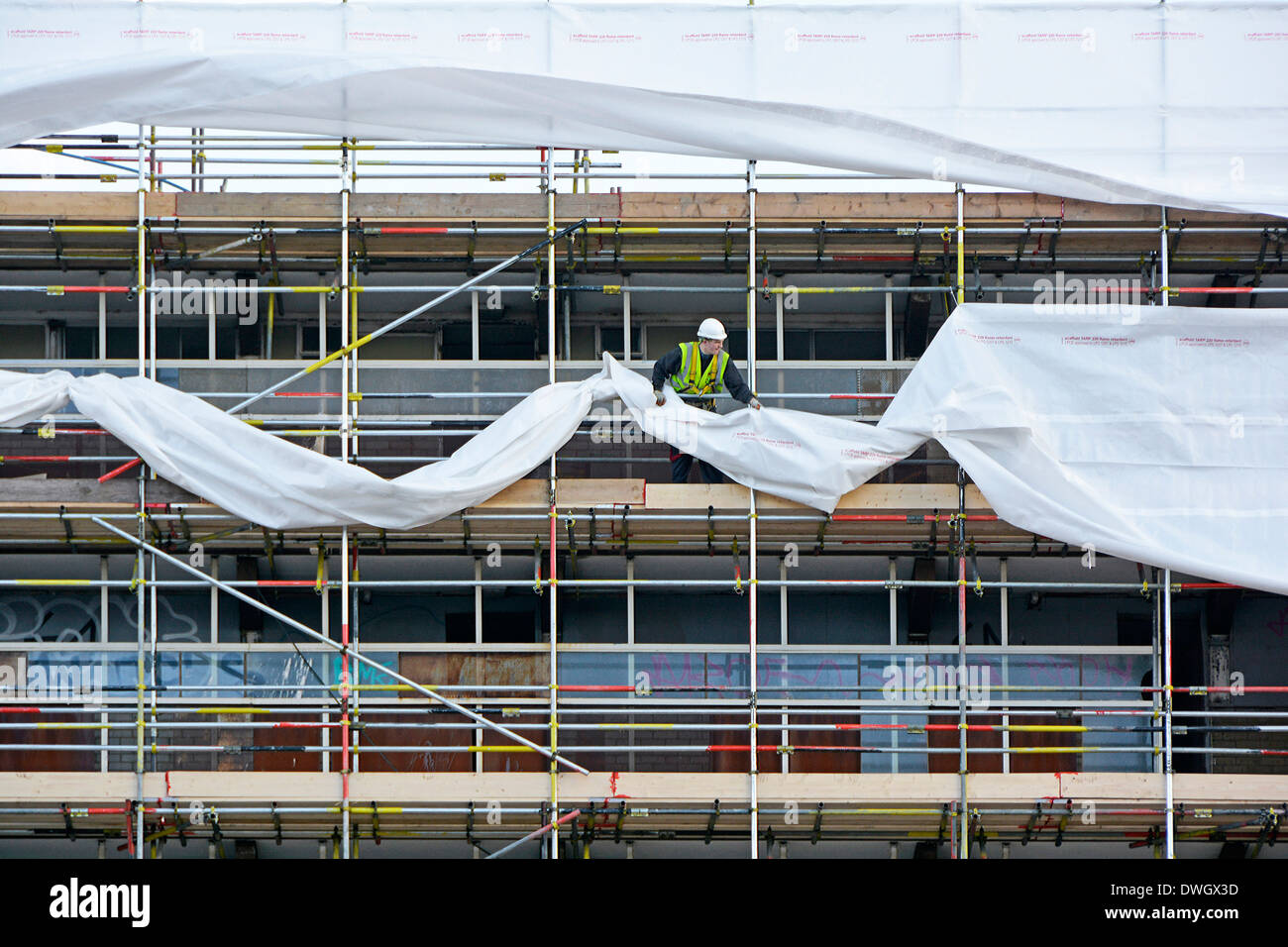 Workman fixing plastic sheeting cocoon to scaffolding erected around high rise housing block prior to demolition Southwark South London England UK - Stock Image