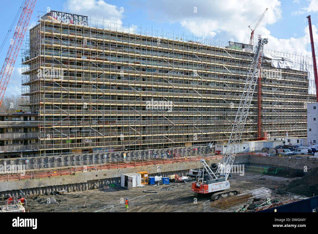 Scaffold around Heygate Estate social housing block preparing for demolition foundation work on previously cleared area Southwark South London England - Stock Image