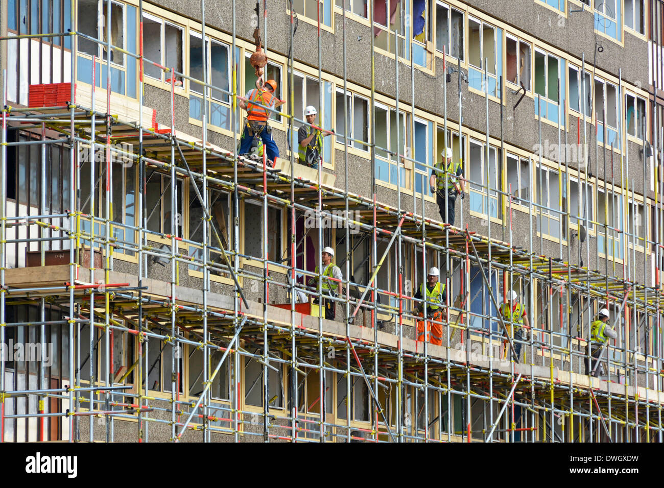 Scaffolders working on one of the empty Heygate Estate high rise social housing blocks in preparation for demolition Southwark South London England UK - Stock Image