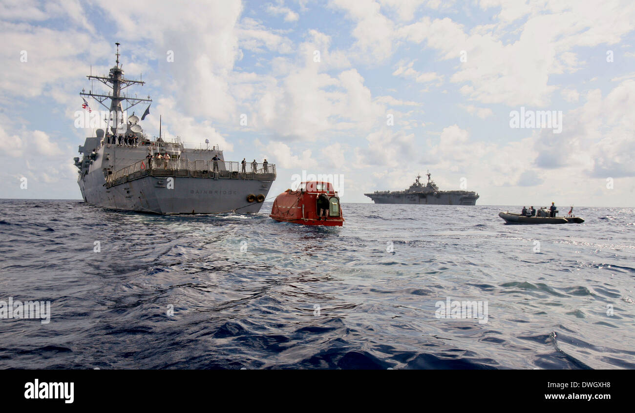 US Navy guided-missile destroyer USS Bainbridge tows the lifeboat from the Maersk Alabama to be processed for evidence after the successful rescue of Capt. Richard Phillips April 13, 2009 in the Indian Ocean. Phillips was held captive by suspected Somali pirates in the lifeboat for five days after a failed hijacking attempt off the Somali coast. - Stock Image