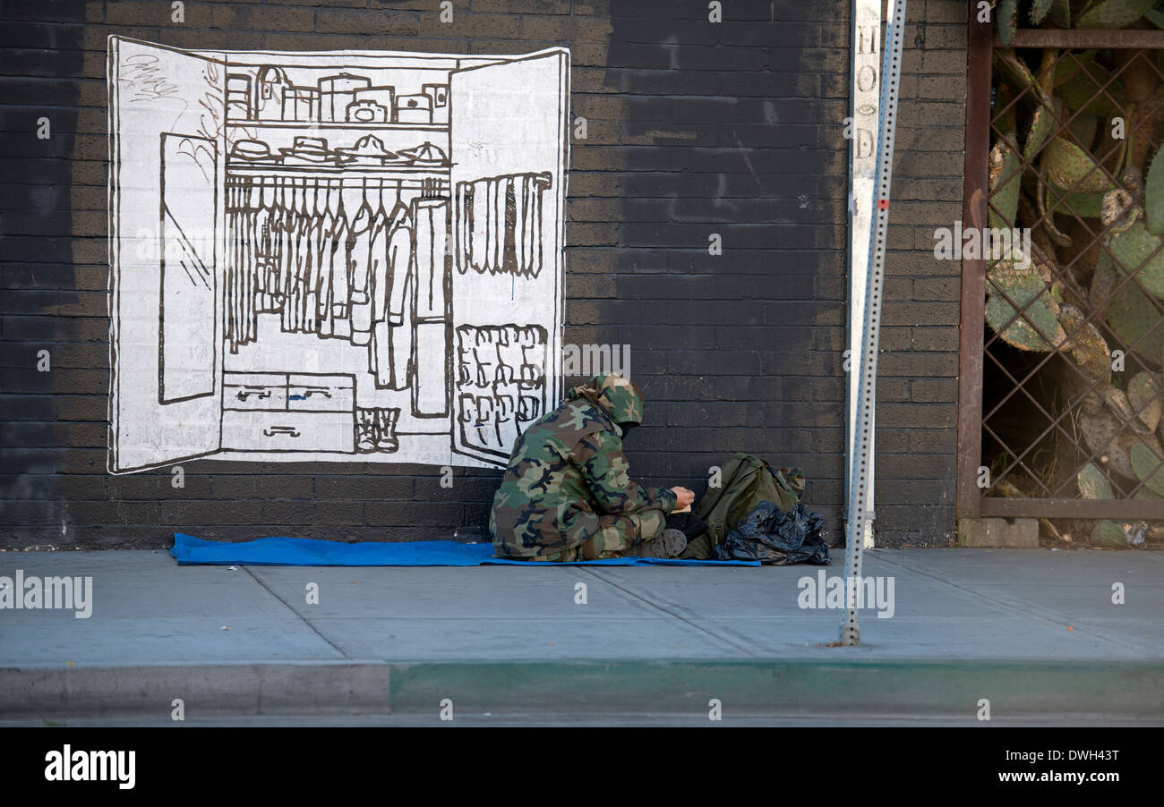 Homeless man sitting on sidewalk next to mural of clothes closet, East Village, San Diego, California - Stock Image