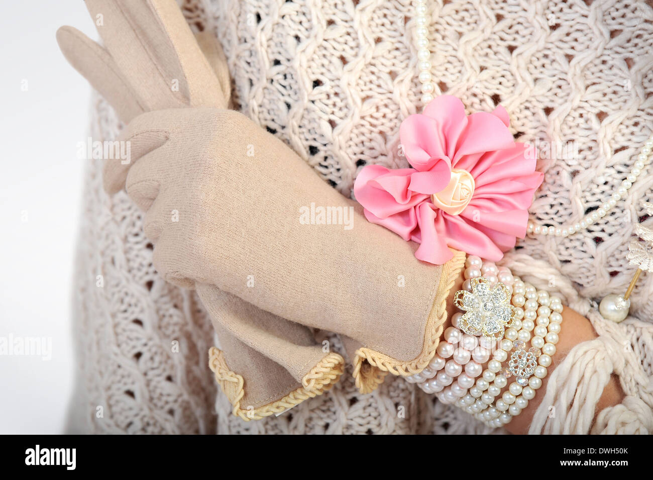 Close-up of woman's hands with elegant beige gloves and jewellry - Stock Image