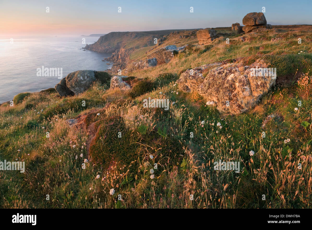 A hazy sun sets over Sennen Cove at Land's End, Cornwall in Summer. Stock Photo