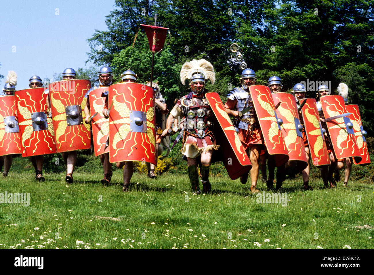 Historical re-enactment, Roman legionary soldiers soldier military cohort attacking, 1st century Army in Britain legion legions armour shields weapons England UK - Stock Image
