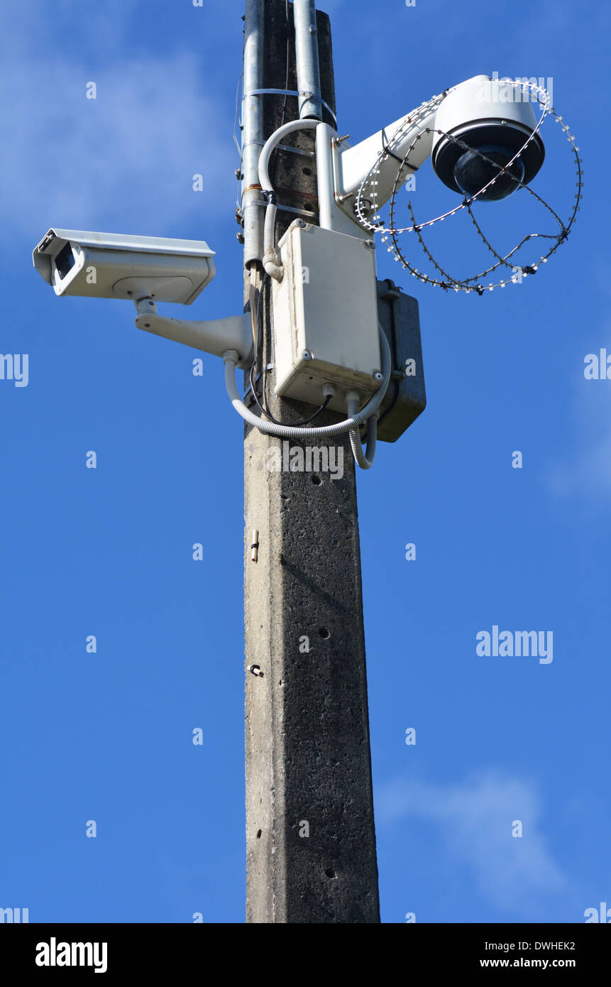 Two security surveillance cameras on a high pole at the park.concept photo of security. - Stock Image