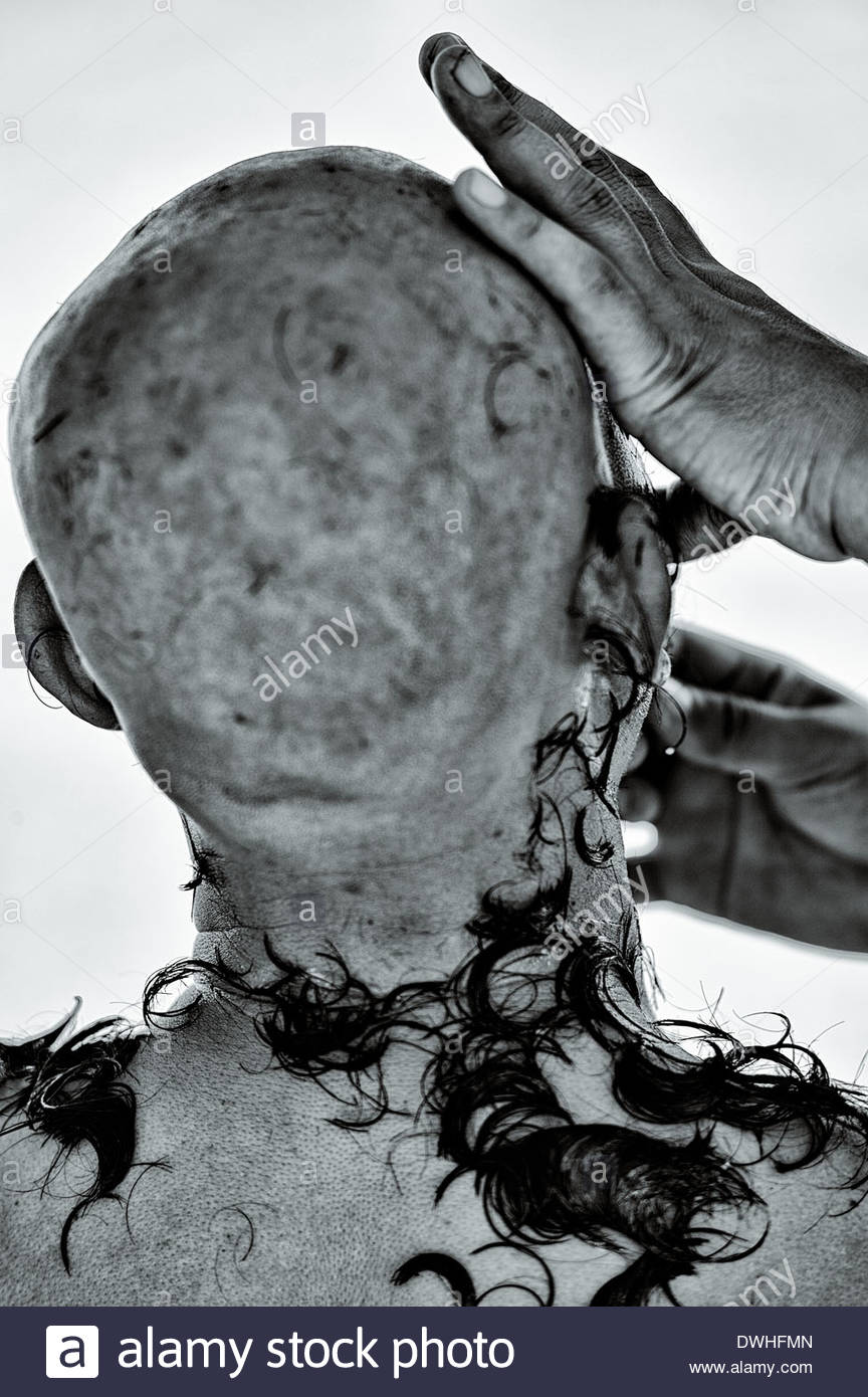 A novice Buddhist Monk has his head shaved at a temple in Bangkok, Thailand. - Stock Image