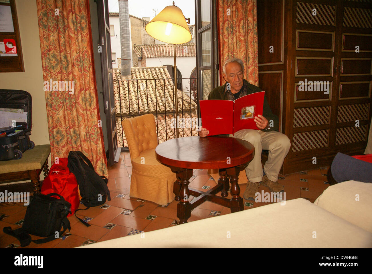 Mature man in his hotel room after a day of siteseeing. Photographed in Ubeda, Spain. Model release available - Stock Image