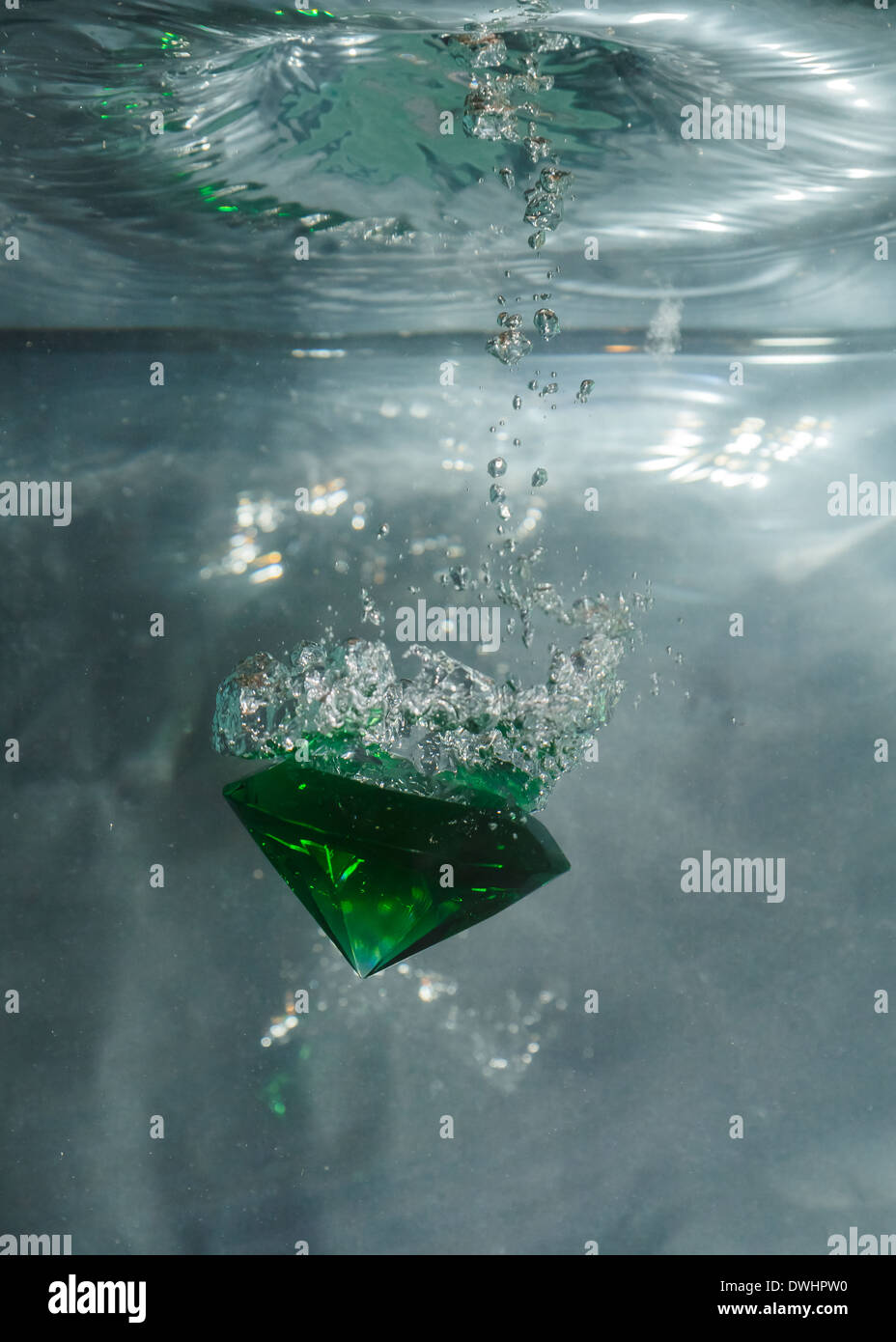 Green emerald falling through the water against a grey background - Stock Image