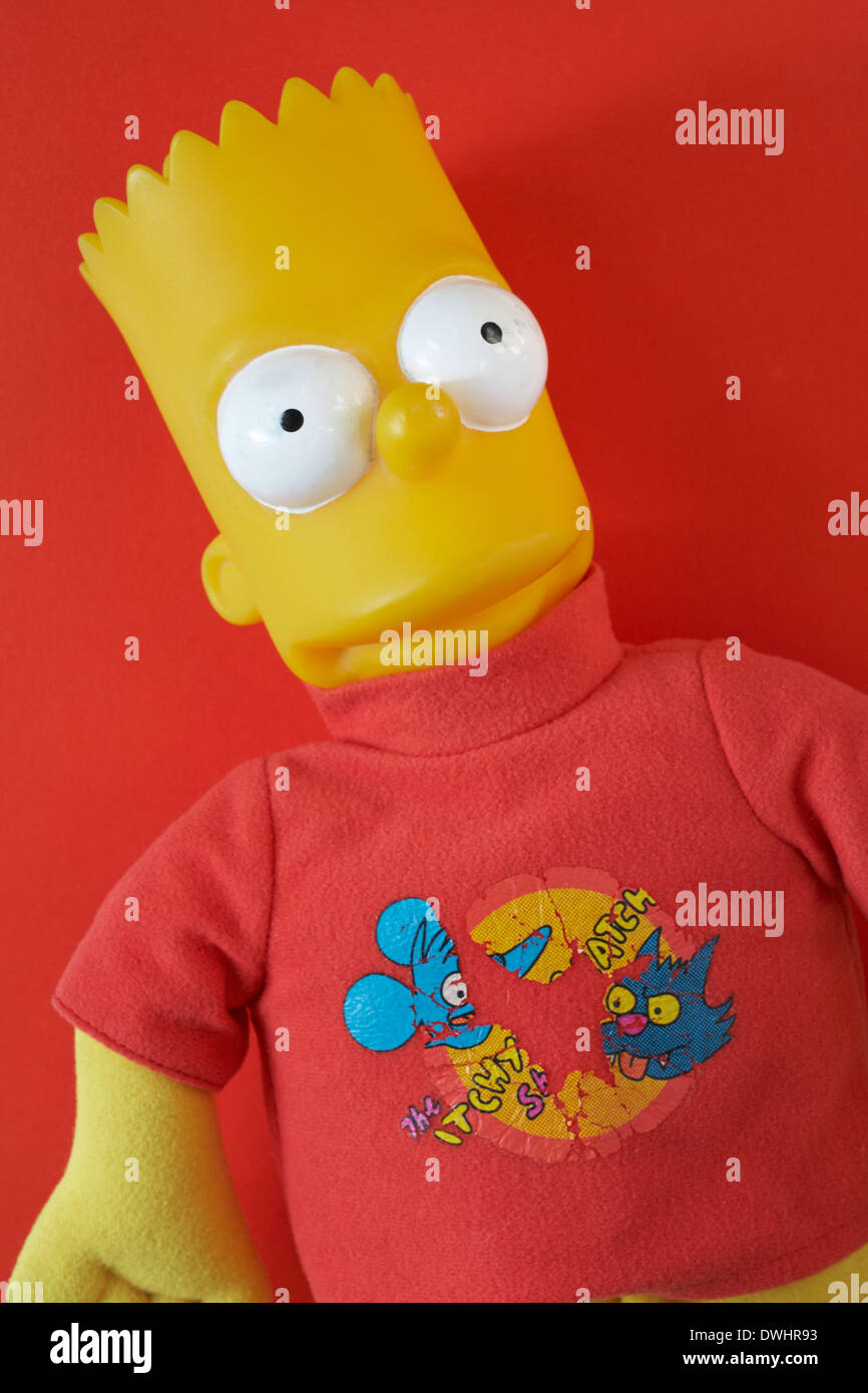 well worn Bart Simpson plastic doll set against red background - Stock Image