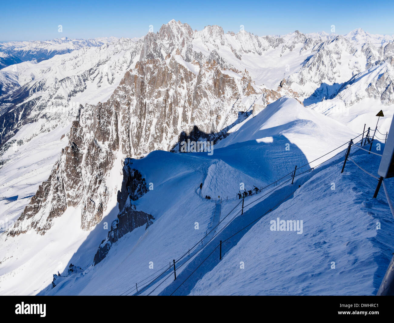 Roped path route to Vallee Blanche with skiers descending arete on Aiguille du Midi Chamonix Haute Savoie Rhone-Alpes France - Stock Image