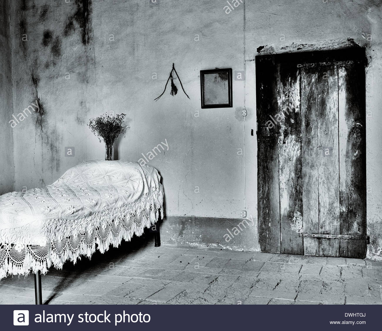 A vase of flowers on the pillow of a bed, on the wall hangs a water diviner,  in an old house in Tuscany, Italy. - Stock Image