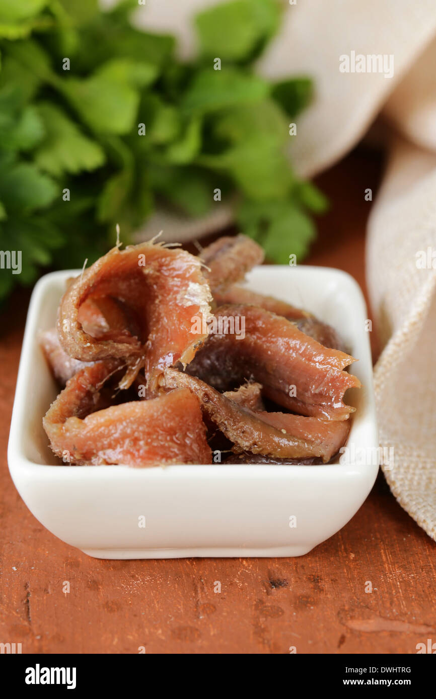 Canned marinated anchovies fillets in a white bowl - Stock Image