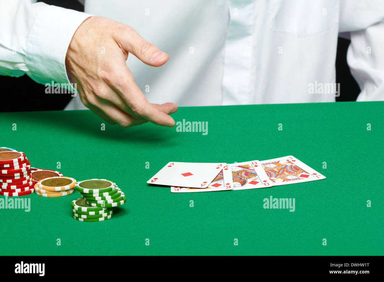 gambler. Male hand with cards and chips on green table - Stock Image