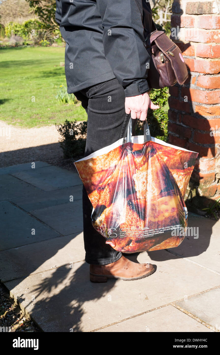 1eb0c64f9ceb Woman carrying heavy shopping in recycled plastic carrier shopping bag from  marks and spencer M