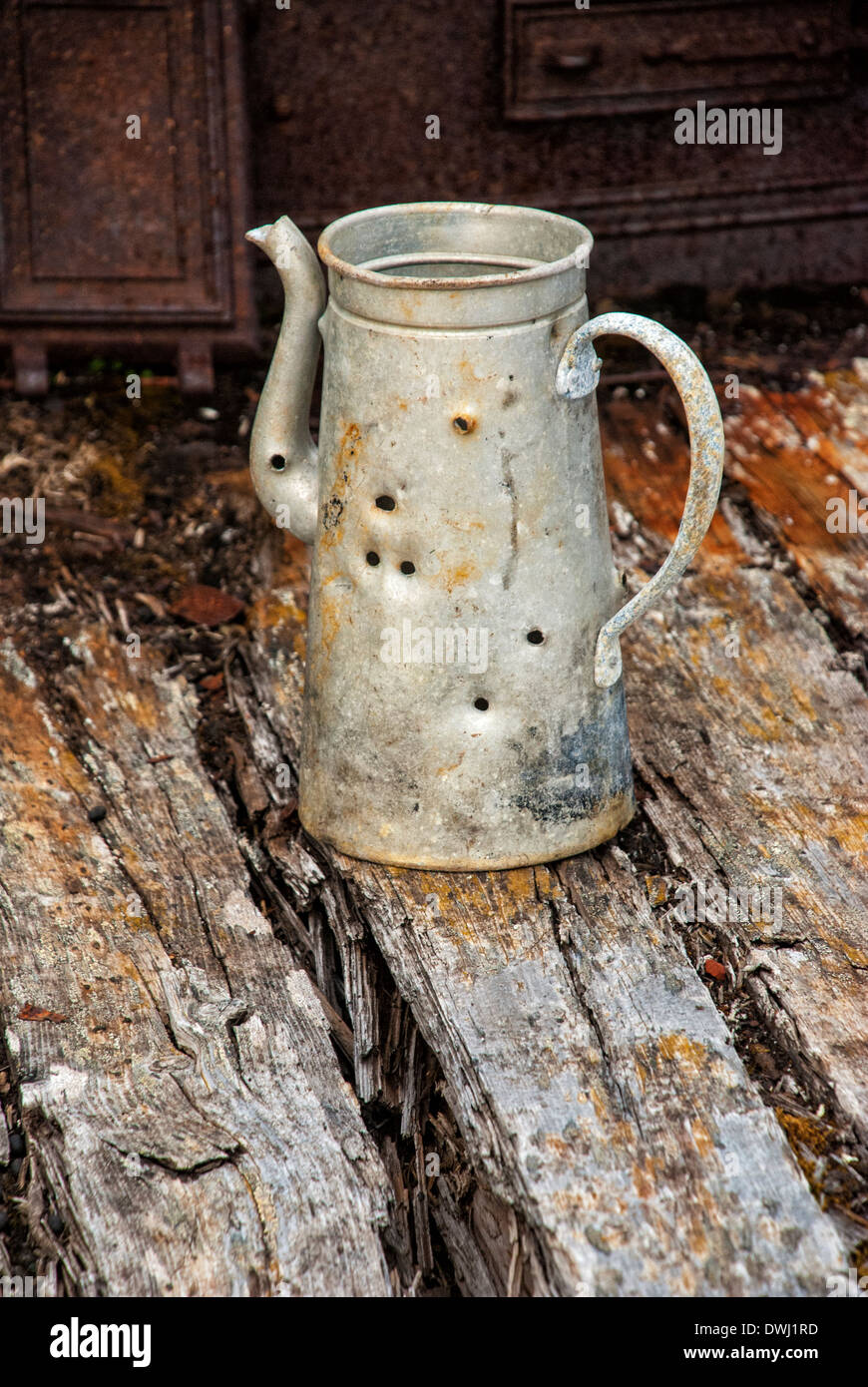 Old tin kettle with bullet holes at abandoned marble quarry, Camp Mansfield, Blomstrandhalvoya, Svalbard Archipelago, Stock Photo