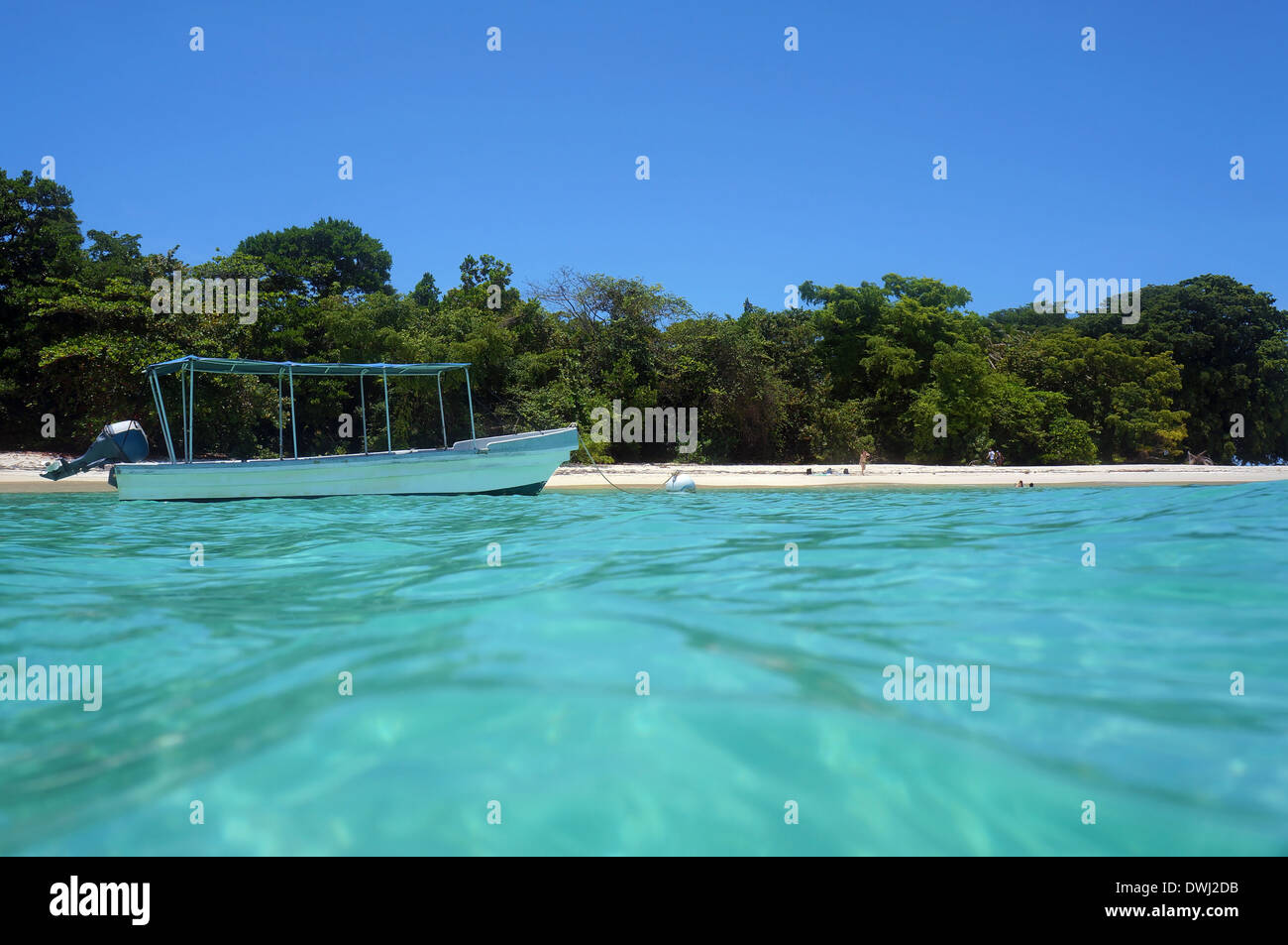 From water surface, boat on mooring buoy near an untouched tropical beach with few tourists, Caribbean sea - Stock Image