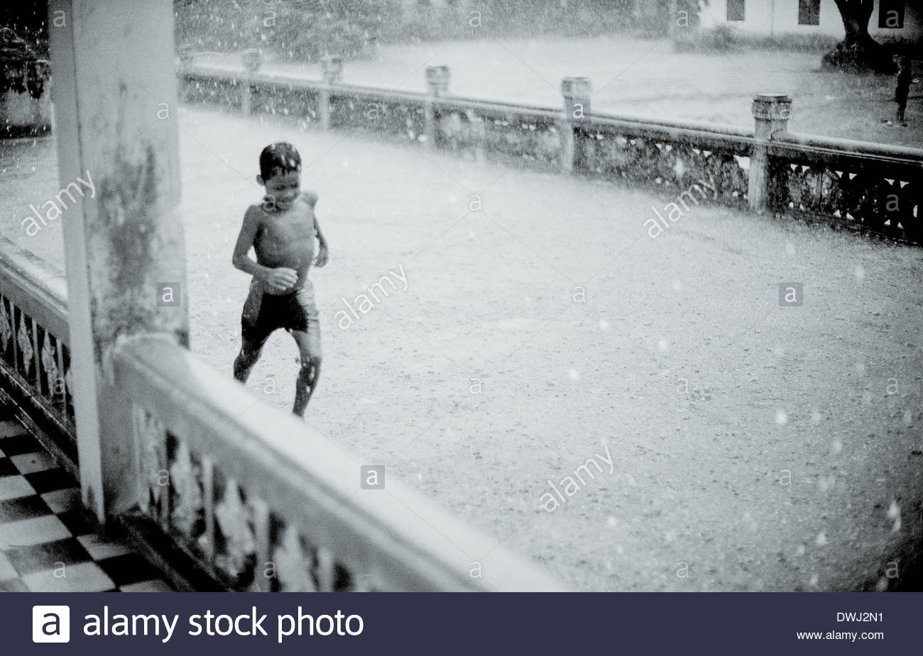 A boy running in the monsoon rains at Angkor Wat, Siem Reap province, Cambodia, South East Asia. - Stock Image